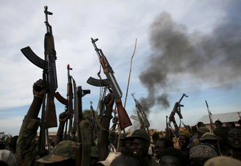 File photo: Rebel fighters hold up their rifles as they walk in front of a bushfire in a rebel-controlled territory in Upper Nile State. (Reuters)